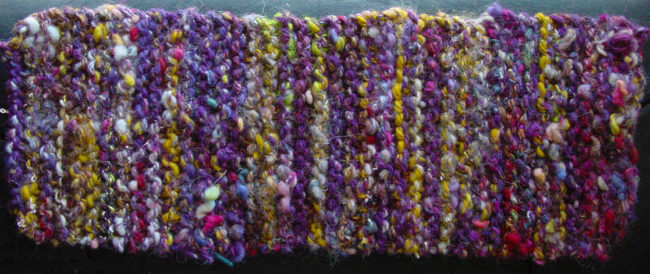 Handspun art yarn knitted into a garter stitch rectangle