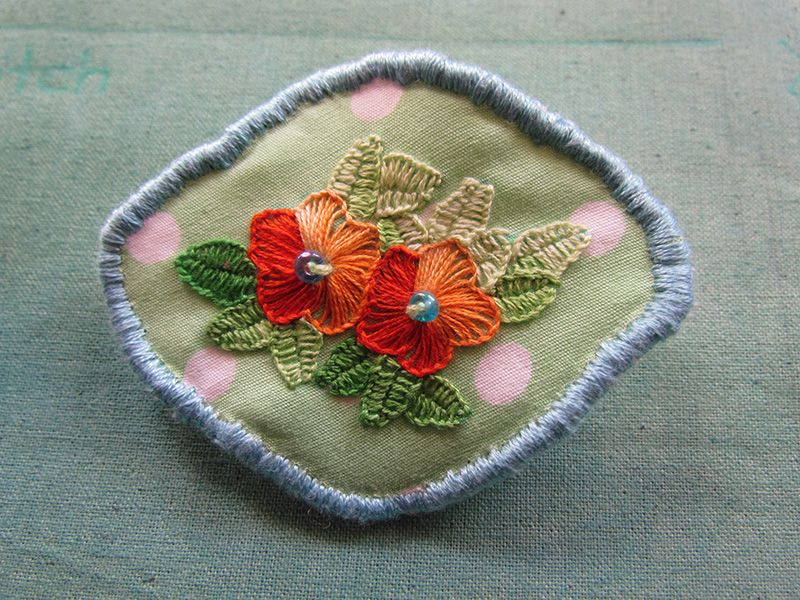 Tiny fabric brooch with flowers worked in buttonhole stitch