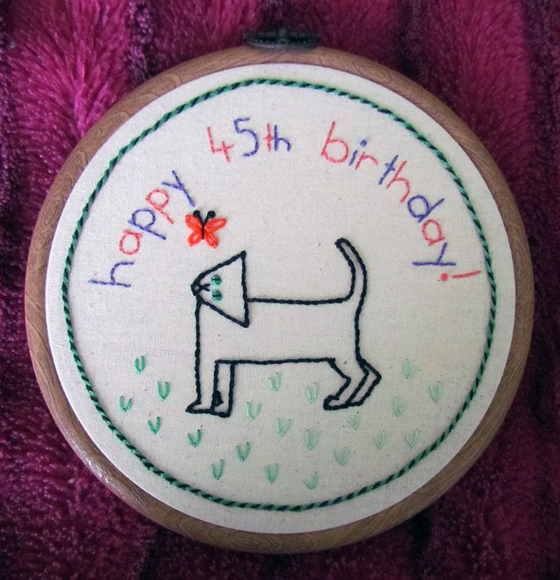 Embroidered medallion with black cat looking at a butterfly and a whipped chain stitch border