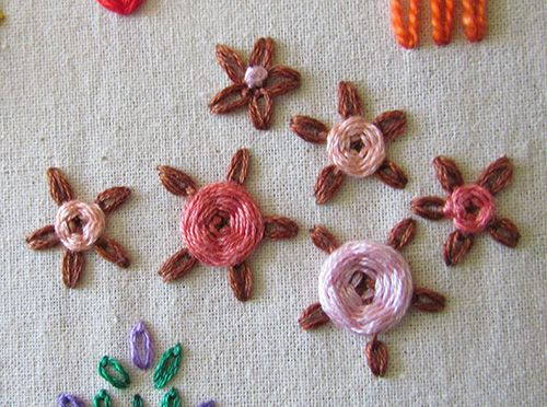 Long tack chain stitch flowers with woven and french knot centres.