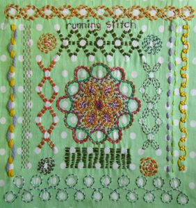 Embroidered running stitch sampler on green fabric with white spots.