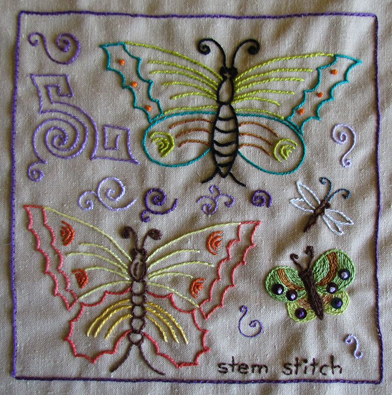 Embroidered sampler with butterflies and curlicues worked in stem stitch