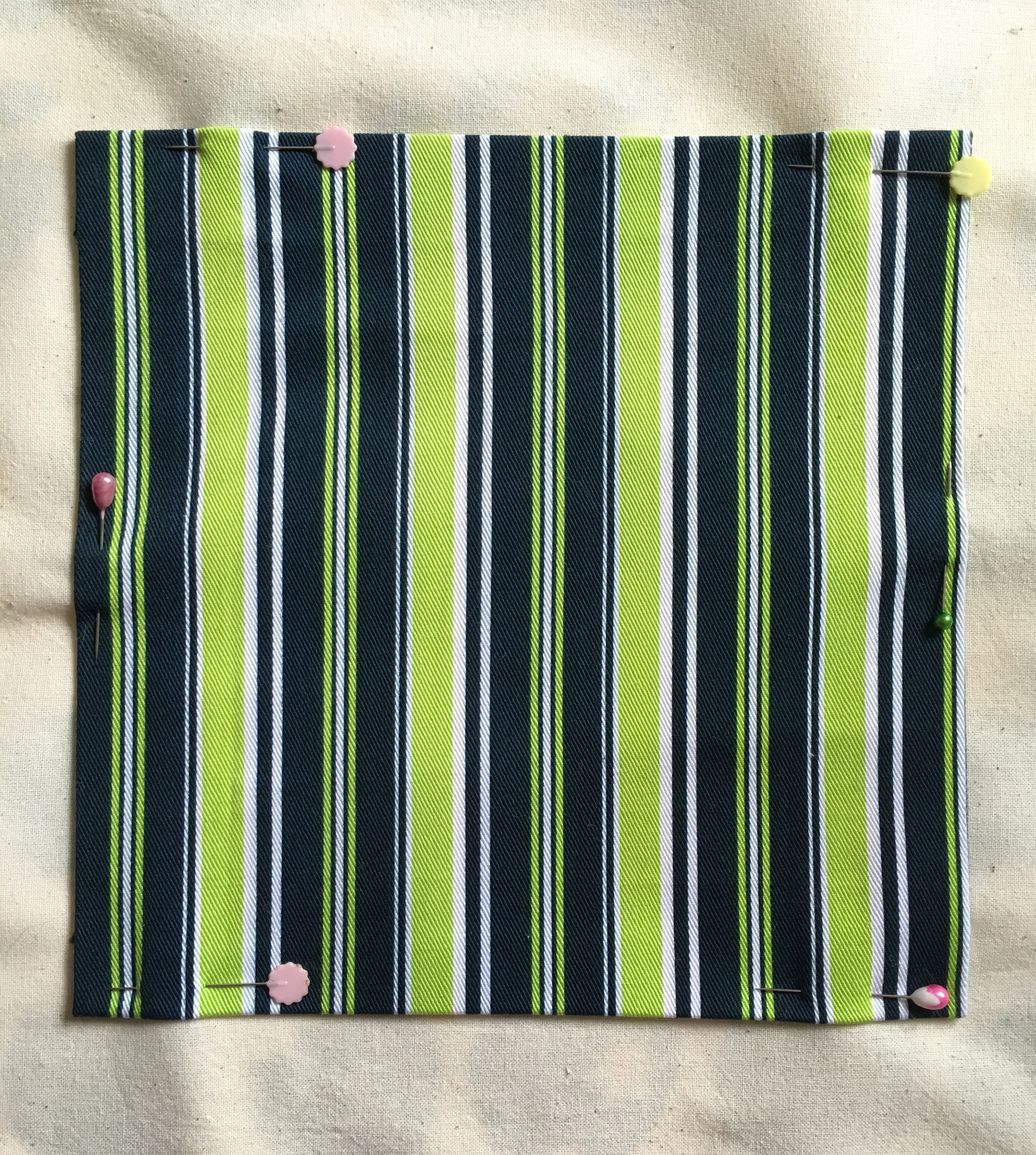 A square of navy blue, lime and white striped twill cotton fabric pinned to a background of unbleached calico.