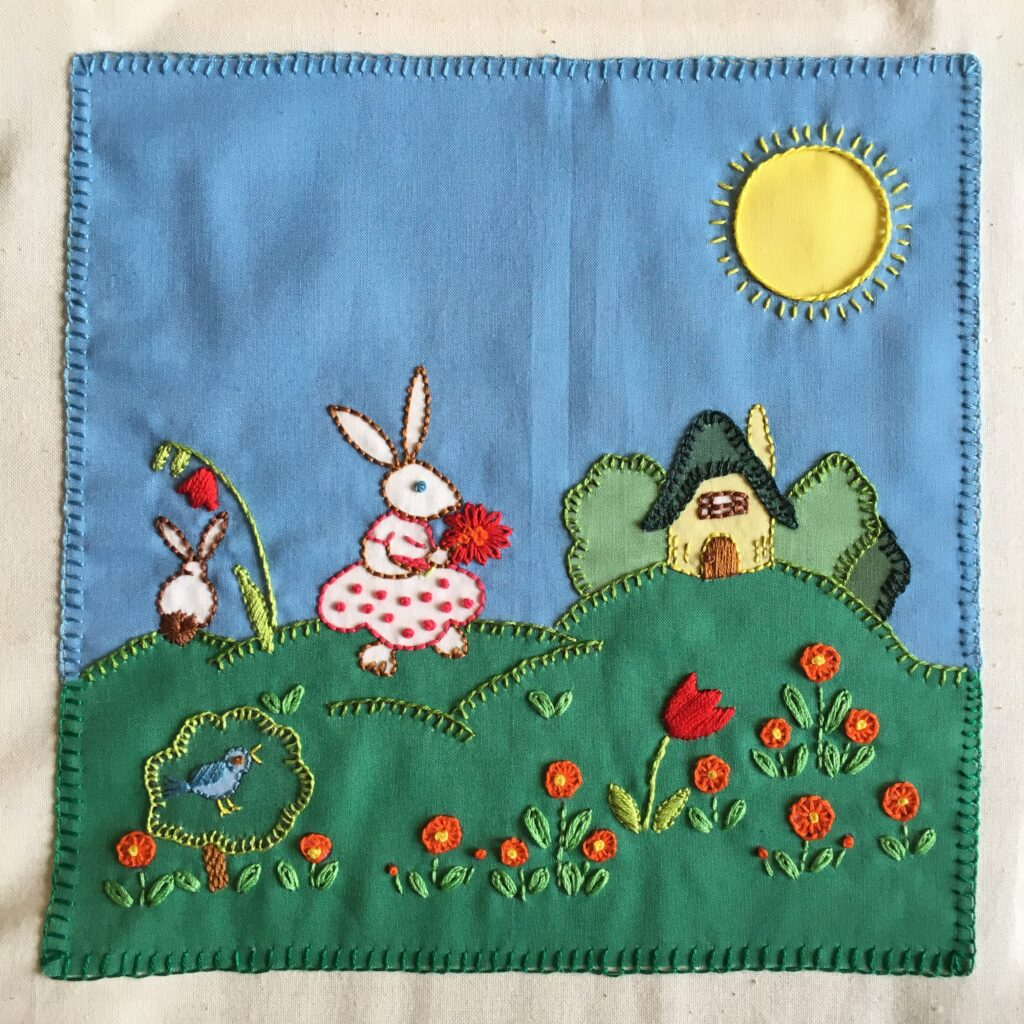 Embroidered square with two rabbits on a garden and a small house