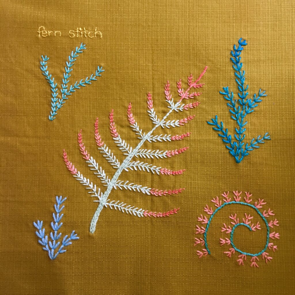 Fern stitch leaves and spirals embroidered on a vintage linen serviette.