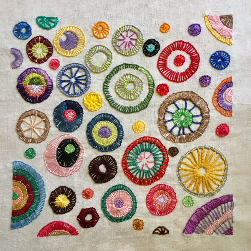 Embroidered sampler with many circles stitched with buttonhole or blanket stitch.
