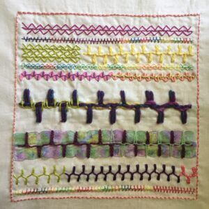Embroidery sampler on calico featuring alternating up and down buttonhole stitch.