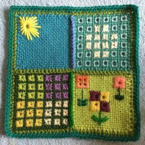 An embroidered garden worked in Algerian eye stitch on pin loom squares. Four 4 inch squares are crocheted together to form an 8 inch sampler.