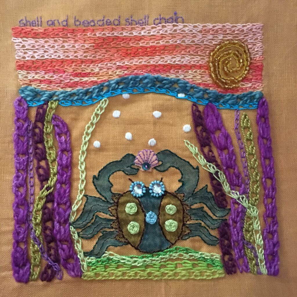 Embroidery sampler featuring a crab sitting on the ocean floor. Featuring shell chain and beaded shell chain stitches.