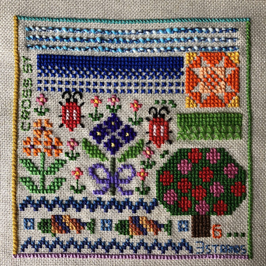 Counted cross stitch sampler worked with a variety of threads.