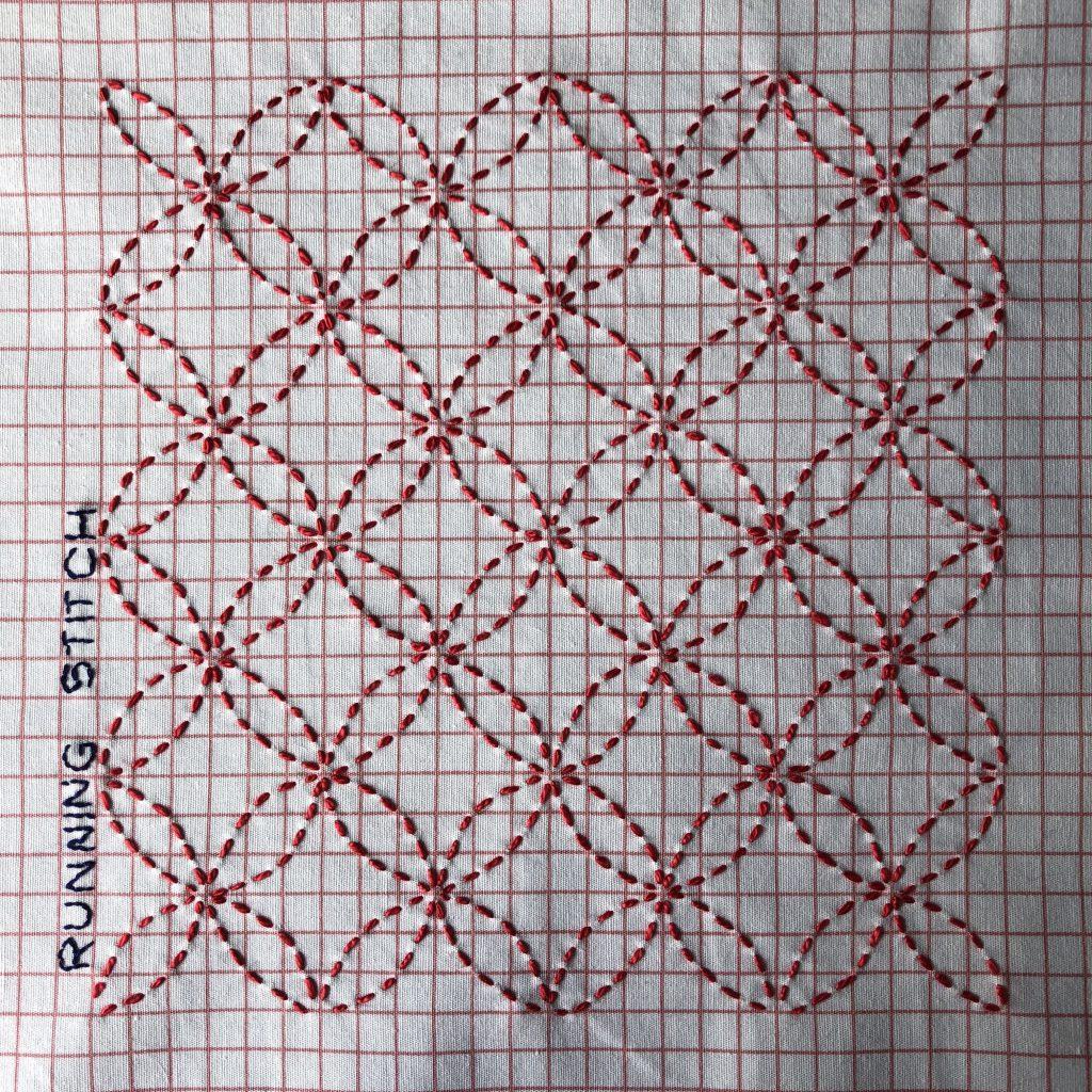 Embroidered sashiko sampler on red check fabric.