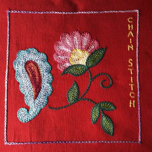 Flower and paisley embroidered with chain stitch filling.