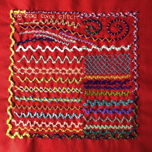 Zig-zag coral stitch worked in a variety of threads on red even weave fabric.