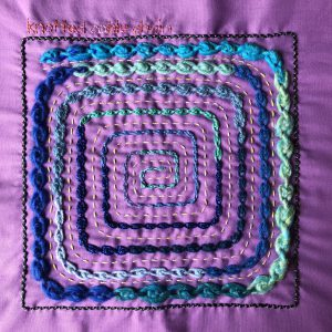 A square spiral of knotted cable chain, worked in a variety of threads.