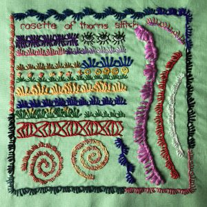 Embroidered motifs and border treatments worked in rosette of thorns stitch.