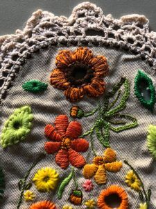 Embroidered flower with an eyelet centre stitched on a piece of found embroidery.