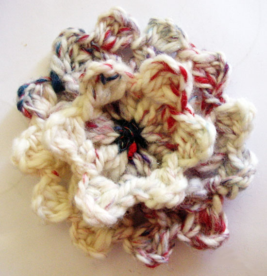 A custer stitch crochet flower made on a loom