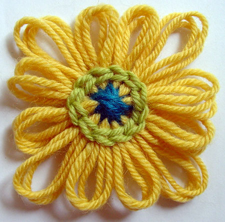 The finished yarn flower with a round of chain stitch worked.