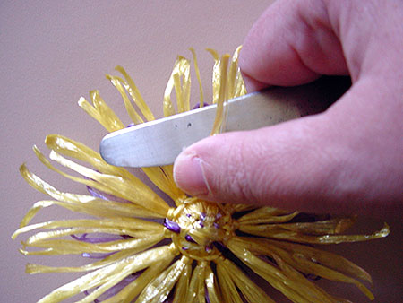 Pulling a knife blade along the petals to curl them