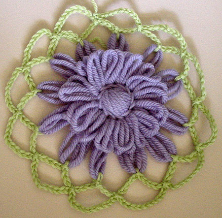 The first loomed flower wih two rounds of crochet