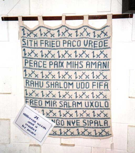 Knitted blanket with the word for eace in many languages