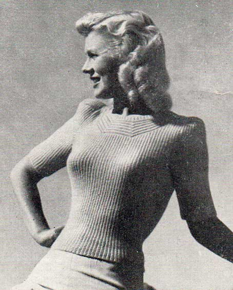 Fitted, garter stitch rib lady's jumper with neckline detail, and puffed sleeves.