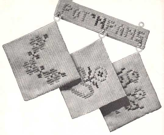 Three cross stitched potholders with flower motifs hanging on a rack with pot n pans embroidered on it