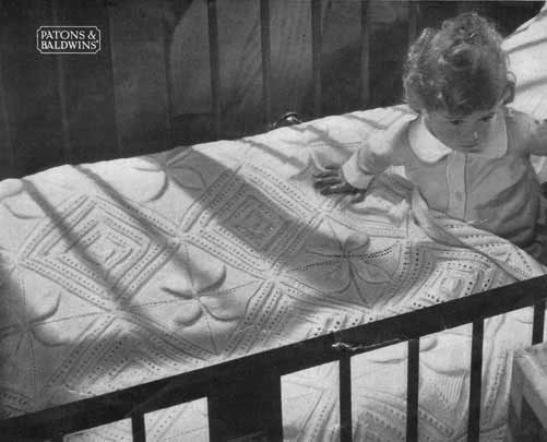 Baby in a cot with a hand knit bedspread with lace and embossed leaf design.