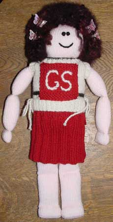 Hand knit doll wearing a netball uniform