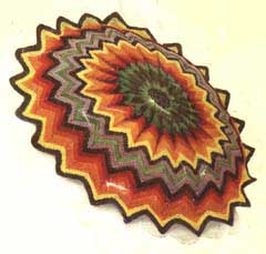Striped crochet cushion cover in a sunburst design
