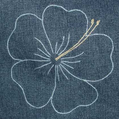 Denim cushion with an embroidered hibiscus