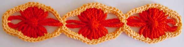 Three lozenge shaped flowers with crocheted edging