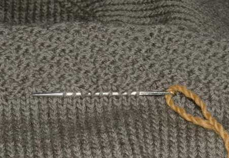 Darning needle threaded with a length of yarn being used to capture the stitches so they don't unravel.