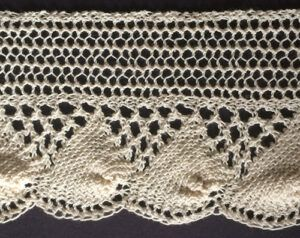 Wide knitted shell lace with eyelet triangles