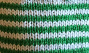 Stocking stitch knitting in rows of green and white stripes