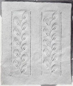 Knitted worsted weight baby blanket with two vertical panels of travelling leaves.
