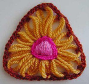A flower made on a triangular flower loom