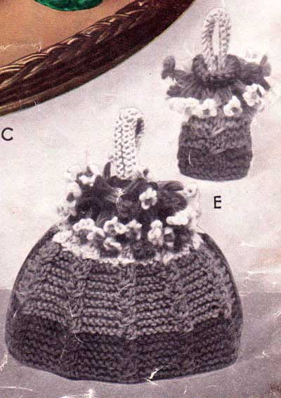 Knitted egg and tea cozies with cabled patterning in the shape of a basket of flowers