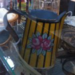 Small tin jug with vertical yellow stripes and flower motif