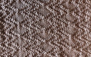 Diamond and zig-zag swatch in knit/purl stitches.