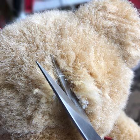 Cutting open the seam on a teddy bear