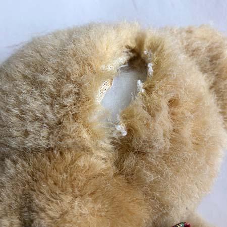 Teddy bear with a seam cut open on the head.