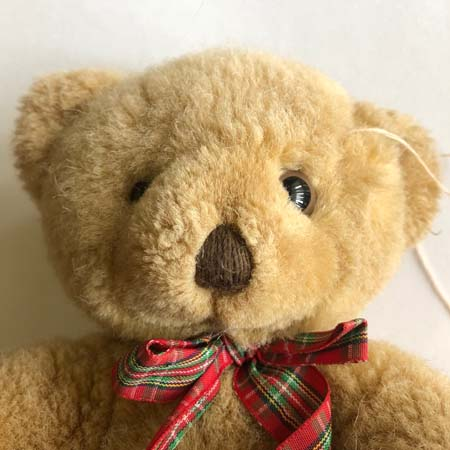 Teddy bear with a new eye and partially sewn seam.