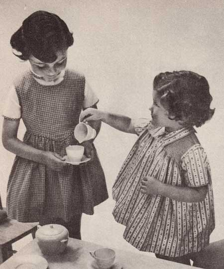 Two little girls wearing a pinafore and a gathered dress