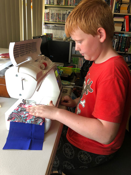 10 year old boy sitting at a sewing machine, making a piece of patchwork.