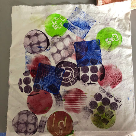 Gelli printed fabric with a random design of squares and circles.