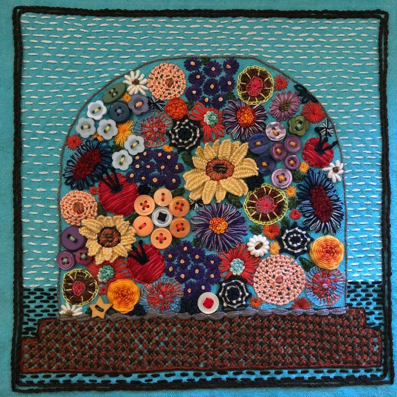 Embroidered sampler of a glass dome filled with flowers