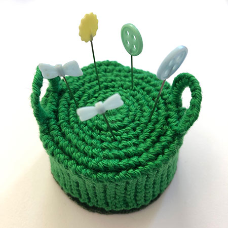 Hand knit pincushion in the shape of an Edwardian hassock with handles