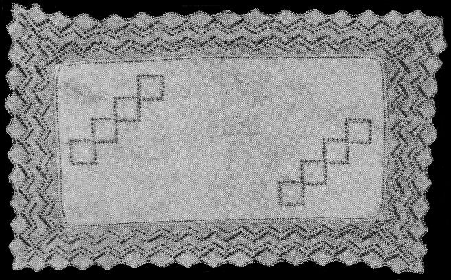An embroidered linen doily with knitted lace edging featuring a design of diamonds and zig-zags