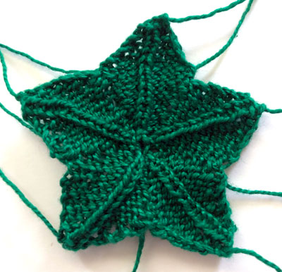 A green, star shaped piece of knitting used to form the leaves on the strawberry pincushion.